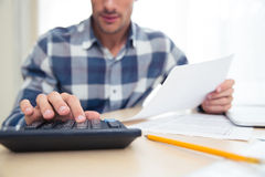 Man with calculator checking bills. Closeup portrait of a man with calculator checking bills at home Royalty Free Stock Images