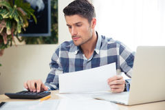 Man with calculator checking bills Royalty Free Stock Photo