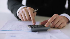 Man with calculator filling a form Stock Photography