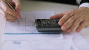 Man with calculator filling a form stock video footage