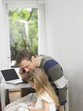 Man On Call As He Looks At Girl Doing Homework Royalty Free Stock Photos