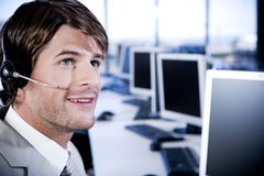 Man with a call centre headset on in a contemporary office Royalty Free Stock Image