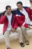 Man On Call With A Friend Sitting With Him Royalty Free Stock Photos