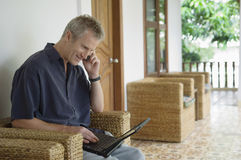 Man On Call While Using Laptop In Patio Royalty Free Stock Image