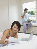 Man On Call By Window And Woman Reading In Bed Royalty Free Stock Photography