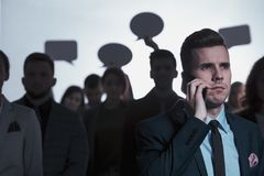 Man calling in a crowd. Serious men calling and standing against a crowd holding speech bubbles Stock Photo