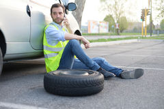 Man calling help service for a flat tyre. After vehicle breakdown Stock Photo