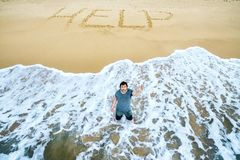 Man is calling for help on uninhabited island. A man is calling for help on the beach of an uninhabited island. Inscription HELP on the sand Stock Photo