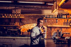 Man calling his business partner while working remotely from bar. Calling business partner. Handsome dark-haired man calling his business partner while working stock photography