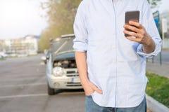 Man calling mechanic after car breakdown Stock Image