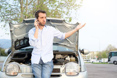 Man calling mechanic after car breakdown. Man calling mechanic help service after car engine breakdown Royalty Free Stock Photography