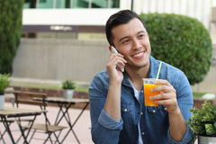 Man calling by phone while enjoying a nice drink outside.  Stock Images
