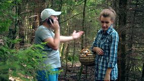Man calling phone. Upset woman standing with basket full of mushrooms. Man calling phone to find way out from forest. Upset woman standing with basket full of stock video