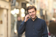 Man calling on the phone walking on the street. Front view of a happy man calling on the phone walking on the street Stock Photos