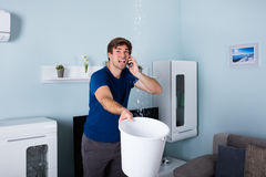 Man Calling Plumber. Worried Man Calling Plumber While Leakage Water Falling Into Bucket At Home Royalty Free Stock Images