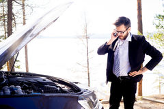 Man calling roadside assistance. An upset young man calling roadside assistance royalty free stock image
