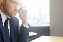Man calling. Serious employer with smartphone calling at break Royalty Free Stock Image