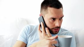Man calling on smartphone in bed at home stock video footage