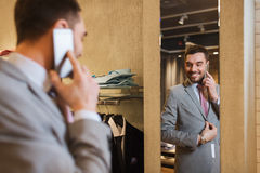 Man calling on smartphone at clothing store mirror Stock Photo