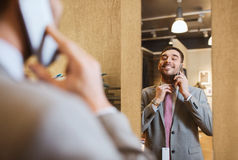Man calling on smartphone at clothing store mirror Stock Images
