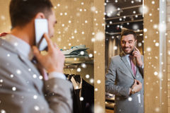 Man calling on smartphone at clothing store mirror Stock Image