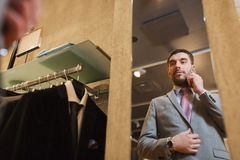 Man calling on smartphone at clothing store mirror Stock Photography