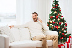 Man calling on smartphone at home for christmas Royalty Free Stock Photography