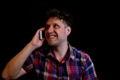 A man is calling and talking on his mobile phone. He has a good mood, he smiles Royalty Free Stock Images