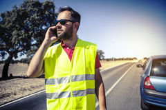 Man calling to insurance company after a car breakdown. Royalty Free Stock Images