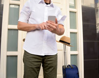 Man calling to the taxi. Man is calling to the taxi with the smartphone and waiting at the doorway of home with the suitcase and pink hat to go in vacations Royalty Free Stock Photography