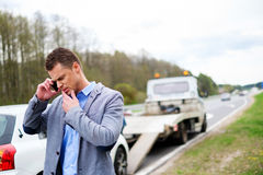 Man calling while tow truck picking up his broken car.  Stock Photography