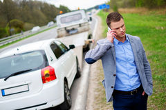 Man calling while tow truck picking up his broken car.  Royalty Free Stock Image