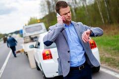 Man calling while tow truck picking up his broken car.  Stock Photos