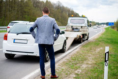 Man calling while tow truck picking up his broken car.  Stock Image