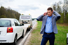 Man calling while tow truck picking up his broken car.  Stock Photo