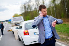 Man calling while tow truck picking up his broken car.  Stock Photos