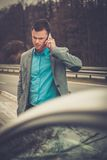 Man calling while tow truck picking up his car Stock Photography