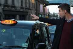 Man calling a traditional British cab royalty free stock images