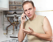 The man calls  to cause the repairman of gas water. The man calls by phone to cause the repairman of gas water heaters Royalty Free Stock Photo