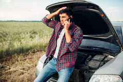 Man calls to service, trouble with vehicle. Man calls to emergency service,while looking on motor of broken car. Trouble with vehicle on road in summer day Royalty Free Stock Images