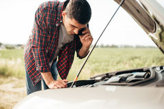 Man calls to service, trouble with vehicle. Man calls to emergency service,while looking on motor of broken car. Trouble with vehicle on road in summer day Royalty Free Stock Photo