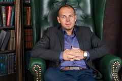 The man, calm and confident businessman sitting in a chair, library.  royalty free stock photography