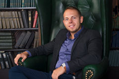 The man, calm and confident businessman sitting in a chair, library Stock Image