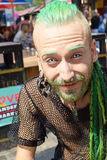 Man at Camden Market London. Man, with dyed green hair and beard, black net vest, posing at Camden market, London in August 2015 Royalty Free Stock Photography