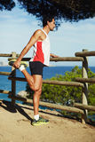 A man came on a morning jog in the mountains, stopped to rest and enjoy the beautiful view of the ocean Stock Photo