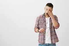 Man came from nightshift and needs some sleep. Portrait of cute unshaven male student yawning and rubbing eyes, being. Exhausted after work, holding glasses in stock image