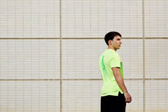 A man came out for a run on the bright day. Portrait of young athletic man standing with his back in bright sportswear against white brick wall background at royalty free stock image