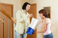 Man came to the elegant woman with a gift at home Stock Photo