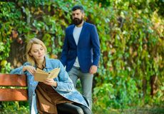 Man came to girlfriend on date. Surprise for her. Girl sit bench read book while wait boyfriend. Romantic relations. Concept. Romantic date. Couple in love royalty free stock photo