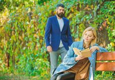 Man came to girlfriend on date. Surprise for her. Girl sit bench read book while wait boyfriend. Romantic relations. Concept. Romantic date. Couple in love royalty free stock photography